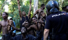2018-07-26 09:02:16 epa06911025 Several migrants celebrate next to a Spanish policeman in Ceuta, Spanish enclave in northern Africa, after they managed to jump the border fence between Spain and Morocco, 26 July 2018. Some 400 migrants reached Spain in a mass jump of the Spanish border early morning despite the holding operation by Spanish and Moroccan security forces. More than a dozen of Spanish Civil Guard officers and five migrants were injured as security force sources said that the migrants acted violently.  EPA/REDUAN